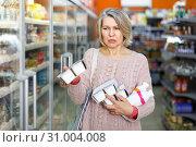 Купить «Mature woman choosing dairy products», фото № 31004008, снято 8 февраля 2019 г. (c) Яков Филимонов / Фотобанк Лори