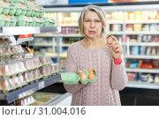 Купить «Dissatisfied woman choosing eggs», фото № 31004016, снято 8 февраля 2019 г. (c) Яков Филимонов / Фотобанк Лори