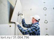 Купить «Tiler installing large format tile on wall. home indoors renovation», фото № 31004796, снято 1 апреля 2019 г. (c) Дмитрий Калиновский / Фотобанк Лори