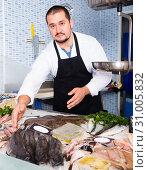 Купить «Standing man shows the fish counter», фото № 31005832, снято 27 октября 2016 г. (c) Яков Филимонов / Фотобанк Лори