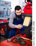 Купить «smiling man worker working at restoring motorbike in workshop», фото № 31005996, снято 19 августа 2019 г. (c) Яков Филимонов / Фотобанк Лори