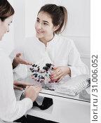 Купить «Female manicurist showing lacquer color schemes», фото № 31006052, снято 2 февраля 2017 г. (c) Яков Филимонов / Фотобанк Лори