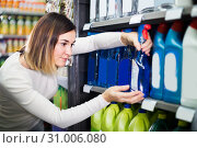 Купить «concentrated girl customer looking for cleaners for home in supermarket», фото № 31006080, снято 23 ноября 2016 г. (c) Яков Филимонов / Фотобанк Лори