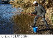 Купить «Afro fisherman pulling fish», фото № 31010564, снято 27 января 2019 г. (c) Яков Филимонов / Фотобанк Лори