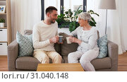 Купить «adult son and senior mother drink coffee at home», видеоролик № 31040148, снято 25 июня 2019 г. (c) Syda Productions / Фотобанк Лори