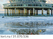 Купить «Building on stone weathered poles at the beach of scheveningen with waves in the sea and reflection in the wet sand», фото № 31070536, снято 2 ноября 2018 г. (c) easy Fotostock / Фотобанк Лори