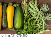 Купить «Fresh organic green vegetables wooden floor with copy space. Green and yellow vegetables background. Healthy eating background. Vegetarian food, organic food.», фото № 31079580, снято 4 июля 2017 г. (c) easy Fotostock / Фотобанк Лори