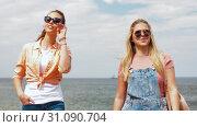 Купить «teenage girls or friends walking at seaside», видеоролик № 31090704, снято 25 июня 2019 г. (c) Syda Productions / Фотобанк Лори