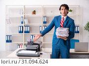 Купить «Young employee making copies at copying machine», фото № 31094624, снято 14 декабря 2018 г. (c) Elnur / Фотобанк Лори