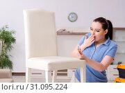 Купить «Young woman repairing chair at home», фото № 31095224, снято 19 марта 2019 г. (c) Elnur / Фотобанк Лори