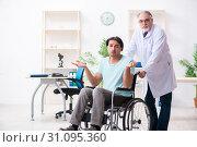 Купить «Male patient in wheel-chair visiting old doctor», фото № 31095360, снято 3 апреля 2019 г. (c) Elnur / Фотобанк Лори