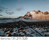 Купить «A road leading towards a mountain through a snow covered landscape in Stokksnes, Iceland. The photo is taken using a drone.», фото № 31211520, снято 1 января 2018 г. (c) easy Fotostock / Фотобанк Лори