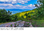 Купить «A beautiful view from the glade with stones to the picturesque mountain slopes with the haze of the blue sky in the midday heat.», фото № 31231656, снято 5 июля 2016 г. (c) easy Fotostock / Фотобанк Лори