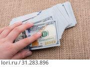 Купить «Hand holding banknote bundle of US dollar on a linen canvas background», фото № 31283896, снято 24 мая 2017 г. (c) easy Fotostock / Фотобанк Лори