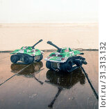 Купить «Two toy tanks on a wooden floor with reflection», фото № 31313132, снято 1 января 2000 г. (c) easy Fotostock / Фотобанк Лори