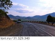 Купить «A steep twist of the wet asphalt road between the lifeless and unsightly mountains in the south», фото № 31329340, снято 7 августа 2011 г. (c) easy Fotostock / Фотобанк Лори