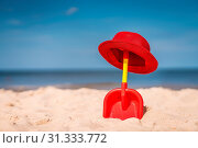 Купить «Red and yellow plastic childrens toy shovel and red straw hat on a beautiful white sand seashore», фото № 31333772, снято 29 марта 2020 г. (c) easy Fotostock / Фотобанк Лори