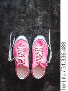 Купить «purple-pink-lilac sneakers with untied laces on a dark concrete background. Copy space. View from above.», фото № 31336488, снято 14 апреля 2019 г. (c) Tetiana Chugunova / Фотобанк Лори
