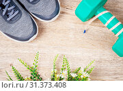 Купить «Flat lay sports composition with grey sneakers, dumbbell and flower on wooden background. Concept healthy lifestyle, sport and diet. Top view.», фото № 31373408, снято 29 мая 2018 г. (c) easy Fotostock / Фотобанк Лори