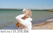 Купить «senior woman drinking shake on summer beach», видеоролик № 31379356, снято 1 июля 2019 г. (c) Syda Productions / Фотобанк Лори