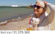 Купить «senior woman drinking shake on summer beach», видеоролик № 31379360, снято 1 июля 2019 г. (c) Syda Productions / Фотобанк Лори