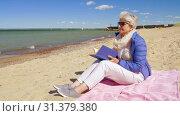 Купить «happy senior woman reading book on summer beach», видеоролик № 31379380, снято 1 июля 2019 г. (c) Syda Productions / Фотобанк Лори