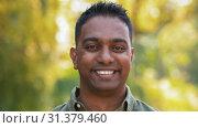 Купить «outdoor portrait of smiling indian man in summer», видеоролик № 31379460, снято 29 июня 2019 г. (c) Syda Productions / Фотобанк Лори