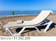 Купить «Concept of rest by the sea - lounger with beach towel and child walking to sea», фото № 31392200, снято 7 июля 2019 г. (c) Светлана Кузнецова / Фотобанк Лори