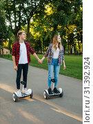 Купить «Male and female person riding on gyroboard in park», фото № 31392924, снято 20 мая 2019 г. (c) Tryapitsyn Sergiy / Фотобанк Лори