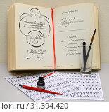Купить «Предметы для занятия каллиграфией на фоне книги по каллиграфическому искусству», фото № 31394420, снято 5 июля 2019 г. (c) Ирина Борсученко / Фотобанк Лори