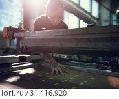 Купить «Man controls wide industrial printer in workshop», фото № 31416920, снято 22 января 2019 г. (c) Pavel Biryukov / Фотобанк Лори