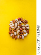 Купить «A variety of nuts are laid out in the shape of a circle on a yellow background. Flat lay. View from above. Copy space. The concept of health care, cardio, proper nutrition, healthy fats», фото № 31421948, снято 19 июня 2019 г. (c) Tetiana Chugunova / Фотобанк Лори