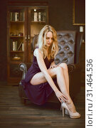 Купить «Sexy young woman in a purple dress sits in a large vintage leather executive chair in an expensive luxury dark interior», фото № 31464536, снято 4 ноября 2017 г. (c) katalinks / Фотобанк Лори