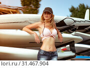 Young beautiful girl at old surfing and windsurfing station stands near the surfboards installed on the racks outdoor. Стоковое фото, фотограф katalinks / Фотобанк Лори