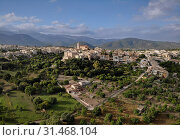 Aerial distant photo drone point of view image Campanet town hillside residential old ancient houses building exterior situated in the northeast of Majorca Island, Spain (2019 год). Стоковое фото, фотограф Alexander Tihonovs / Фотобанк Лори