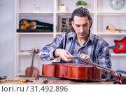 Купить «Young handsome repairman repairing cello», фото № 31492896, снято 4 апреля 2019 г. (c) Elnur / Фотобанк Лори