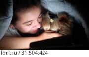 Happy teenage girl with phone under a blanket playing with a dog. Стоковое видео, видеограф Элина Гаревская / Фотобанк Лори