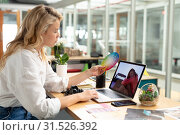 Купить «Female graphic designer looking at color swatch while using laptop at desk», фото № 31526392, снято 17 марта 2019 г. (c) Wavebreak Media / Фотобанк Лори
