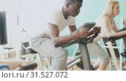 Купить «African man and two Caucasian women exercising on stationary bikes at gym», видеоролик № 31527072, снято 24 марта 2019 г. (c) Яков Филимонов / Фотобанк Лори