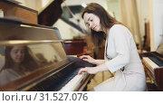 Купить «Beautiful girl chooses a piano in a music store», видеоролик № 31527076, снято 12 мая 2019 г. (c) Яков Филимонов / Фотобанк Лори