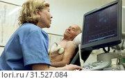 Купить «Hospital woman doctor examines a senior man with ultrasonic device», видеоролик № 31527084, снято 7 июня 2019 г. (c) Яков Филимонов / Фотобанк Лори