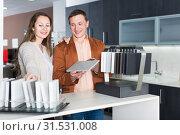 Купить «Young couple customers choosing tabletop», фото № 31531008, снято 4 апреля 2017 г. (c) Яков Филимонов / Фотобанк Лори