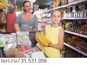 Купить «girl and mom are standing near trolley with groceries», фото № 31531056, снято 5 июня 2017 г. (c) Яков Филимонов / Фотобанк Лори