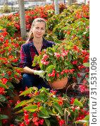 Купить «Woman farmer checking blooming begonias», фото № 31531096, снято 17 июля 2019 г. (c) Яков Филимонов / Фотобанк Лори