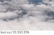 Купить «The view from the flying airplane window on puffy clouds and earth below.», видеоролик № 31531576, снято 13 апреля 2019 г. (c) Serg Zastavkin / Фотобанк Лори