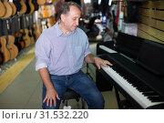 Купить «Smiling musician is playing on modern keyboard», фото № 31532220, снято 18 сентября 2017 г. (c) Яков Филимонов / Фотобанк Лори