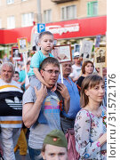 A young father with a son on his shoulders, participants in the action Immortal Regiment. Orenburg, Russia - May 9, 2019: Celebration of Victory Day. Редакционное фото, фотограф Вадим Орлов / Фотобанк Лори