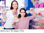 Купить «Mother with happy daughter holding candies in the shop», фото № 31622772, снято 22 января 2018 г. (c) Яков Филимонов / Фотобанк Лори