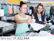Купить «Female friends choosing trousers in shop», фото № 31622844, снято 19 июня 2017 г. (c) Яков Филимонов / Фотобанк Лори