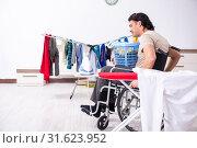 Купить «Young man in wheel-chair doing ironing at home», фото № 31623952, снято 27 марта 2019 г. (c) Elnur / Фотобанк Лори